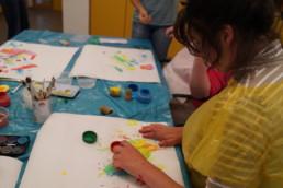 Junge Frau malt zusammen mit anderen im Tagesraum